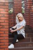 Schönes junges blondes Mädchen mit einem hübschen Gesicht und einem schönen Lächeln mustert Porträt einer Frau mit dem langen Haa Stockfotografie