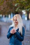 Schönes junges blondes Mädchen mit einem hübschen Gesicht und einem schönen Lächeln mustert Porträt einer Frau mit dem langen Haa Stockbilder