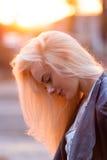 Schönes junges blondes Mädchen mit einem hübschen lächelnden Gesicht und schöne Augen Eine Frau mit dem langen Haar zerstreut ihr Lizenzfreie Stockbilder