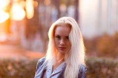 Schönes junges blondes Mädchen mit einem hübschen lächelnden Gesicht und schöne Augen Eine Frau mit dem langen Haar zerstreut ihr Lizenzfreie Stockfotos