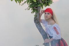 Schönes junges blondes Mädchen mit einem roten Schal, einer traditionellen rumänischen Bluse und einem roten und schwarzen Rock Stockbild