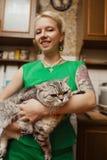 Schönes junges blondes Mädchen mit einer Katze in ihren Armen Stockfoto
