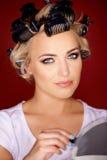 Schönes junges blondes mit ihrem Haar in den Lockenwicklern Stockfoto