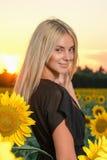 Schönes junges blondes Modell des Porträts im schwarzen Kleid auf einem Feld von Sonnenblumen Stockbilder