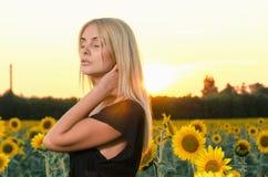 Schönes junges blondes Modell des Porträts im schwarzen Kleid auf einem Feld von Sonnenblumen Lizenzfreie Stockfotografie