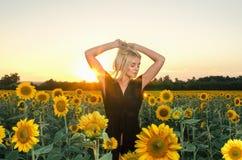 Schönes junges blondes Modell im schwarzen Kleid auf einem Feld von Sonnenblumen Lizenzfreies Stockbild