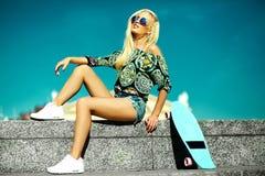 Schönes junges blondes vorbildliches Mädchen im Sommerhippie kleidet mit Skateboard Lizenzfreie Stockfotos
