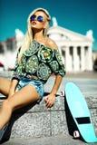 Schönes junges blondes vorbildliches Mädchen im Sommerhippie kleidet mit Skateboard Stockbilder