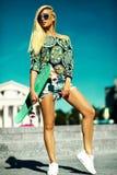 Schönes junges blondes vorbildliches Mädchen im Sommerhippie kleidet mit Skateboard Stockfoto