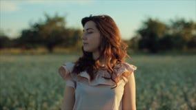 Schönes junges brunette Mädchen im schwarzen Rock gehend auf das Feld Aufstellung vor der Kamera und Berühren des Haares stock video
