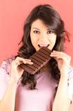Schönes junges Brunettemädchen, das Schokolade isst Stockbild