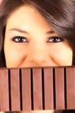 Schönes junges Brunettemädchen, das Schokoriegel isst Lizenzfreies Stockfoto