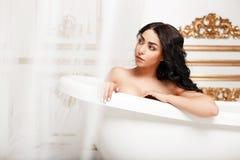 Schönes junges Brunettemädchen mit den Locken, die im Badezimmer stillstehen lizenzfreies stockfoto