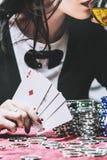 Schönes junges erfolgreiches Spielen der Frau in einem Kasino an einem Tisch