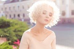 Schönes junges gelocktes blondes Mädchen draußen in der Sonne bei Sonnenuntergang an einem hellen Tag Stockfotografie