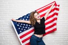 Schönes junges gelocktes Mädchen in der zufälligen Kleidung, die, stehend mit amerikanischer Flagge gegen Backsteinmauer aufwirft Stockbild