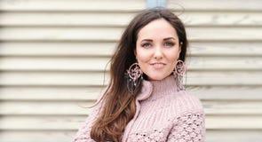 Schönes junges glückliches Frauenporträt, nette leichte Strickjacke und handgemachtes boho reden Ohrringe an stockfotografie