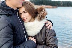 Schönes junges glückliches Paar in der Liebe, die auf dem Ufer des Sees an einem warmen sonnigen Abend umarmt Stockbilder