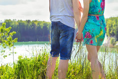 Schönes junges glückliches Paar steht auf der Bank von oneoa an einem sonnigen Tag, einem Mädchen in einem blauen Kleid und dem K Stockfotos