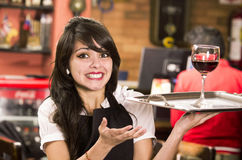 Schönes junges Kellnerinmädchen, das ein Getränk dient Lizenzfreies Stockbild