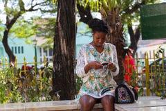 Schönes junges kreolisches kubanisches Frauen-hübsches Blumenmuster-Kleiderdunkle Haut-Versenden von SMS-Nachrichten Santiago De  stockbilder