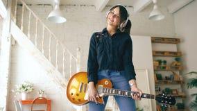 Schönes junges lächelndes Mädchen in den Kopfhörern, die zu Hause mit Studio der E-Gitarre zuhause aufwerfen stock video