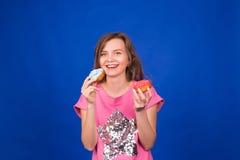 Schönes junges lustiges Mädchen mit Schaumgummiringen auf blauem Hintergrund Ungesundes Diät-, Fertigkost-, Partei- und Feierkonz stockbild