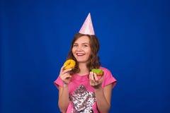 Schönes junges lustiges Mädchen mit Schaumgummiringen auf blauem Hintergrund Ungesundes Diät-, Fertigkost-, Partei- und Feierkonz lizenzfreie stockfotografie