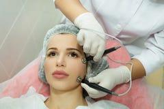 Schönes junges Mädchen auf dem Verfahren der Haut Stockbild