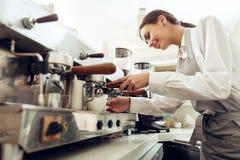 Schönes junges Mädchen barista, das Kaffee zubereitet stockfoto
