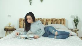 Schönes junges Mädchen, das auf dem Bett liest ein Hochglanzmagazin liegt stock video