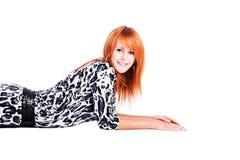 Schönes junges Mädchen, das auf dem Fußboden lächelt stockbild