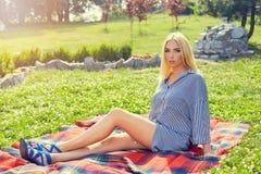 Schönes junges Mädchen, das auf dem Plaid im Park stillsteht Lizenzfreies Stockfoto