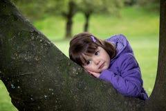 Schönes junges Mädchen, das auf einem Baum stillsteht Stockfotografie