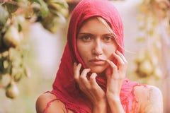 Schönes junges Mädchen, das auf einem roten Schal versucht Herbstzeit für Ernte Obstgarten Das Konzept des Erntens stockbilder