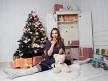 Schönes junges Mädchen, das auf einem Splitter unter Geschenken und einem Weihnachtsbaum sitzt stockfotografie
