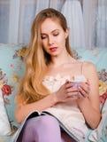 Schönes junges Mädchen, das auf einer Couch, eine Zeitschrift lesend sitzt und Stockbilder