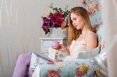 Schönes junges Mädchen, das auf einer Couch sitzt, eine Zeitschrift liest und Kaffee und Lächeln trinkt Lizenzfreie Stockbilder