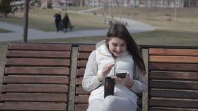 Schönes junges Mädchen, das auf einer Holzbank in einem Stadt Park in einem trinkenden Kaffee der weißen Klage von einem thermisc stock video footage