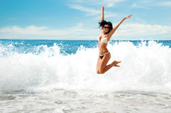 Schönes junges Mädchen, das auf Meer springt Stockfotos