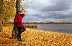 Schönes junges Mädchen, das am Baum sich lehnt lizenzfreie stockfotografie