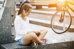 Schönes junges Mädchen, das in den Kopfhörern mit Tablette im Park sitzt stockfoto