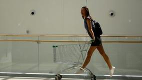 Schönes junges Mädchen, das den Spaß fährt auf Einkaufswagen am Supermarkt hat Zeitlupeschu? stock video