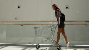 Schönes junges Mädchen, das den Spaß fährt auf Einkaufswagen am Supermarkt hat Zeitlupeschu? stock video footage