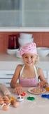 Schönes junges Mädchen, das in der Küche arbeitet Stockbild