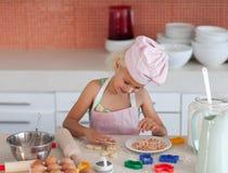 Schönes junges Mädchen, das in der Küche arbeitet Lizenzfreie Stockbilder