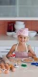 Schönes junges Mädchen, das in der Küche arbeitet Stockbilder