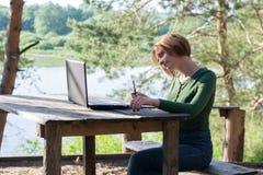 Schönes junges Mädchen, das draußen ihre grafische Tablette verwendet lizenzfreie stockbilder