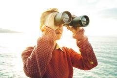 Schönes junges Mädchen, das durch Ferngläser dem Meer auf hellen Sunny Day betrachtet Wanderlust-Reise-Konzept stockfotos
