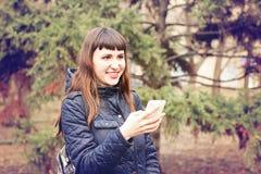 Schönes junges Mädchen, das eine Mitteilung in einem Handy liest Stockbild